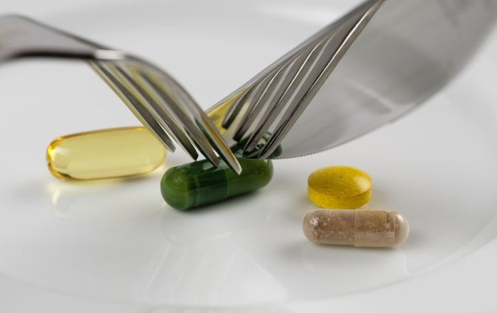 Supplements and vitamins on a plate being cut with a knife and fork